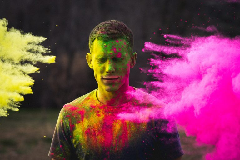 Person having colorful powder stuff thrown at their face.
